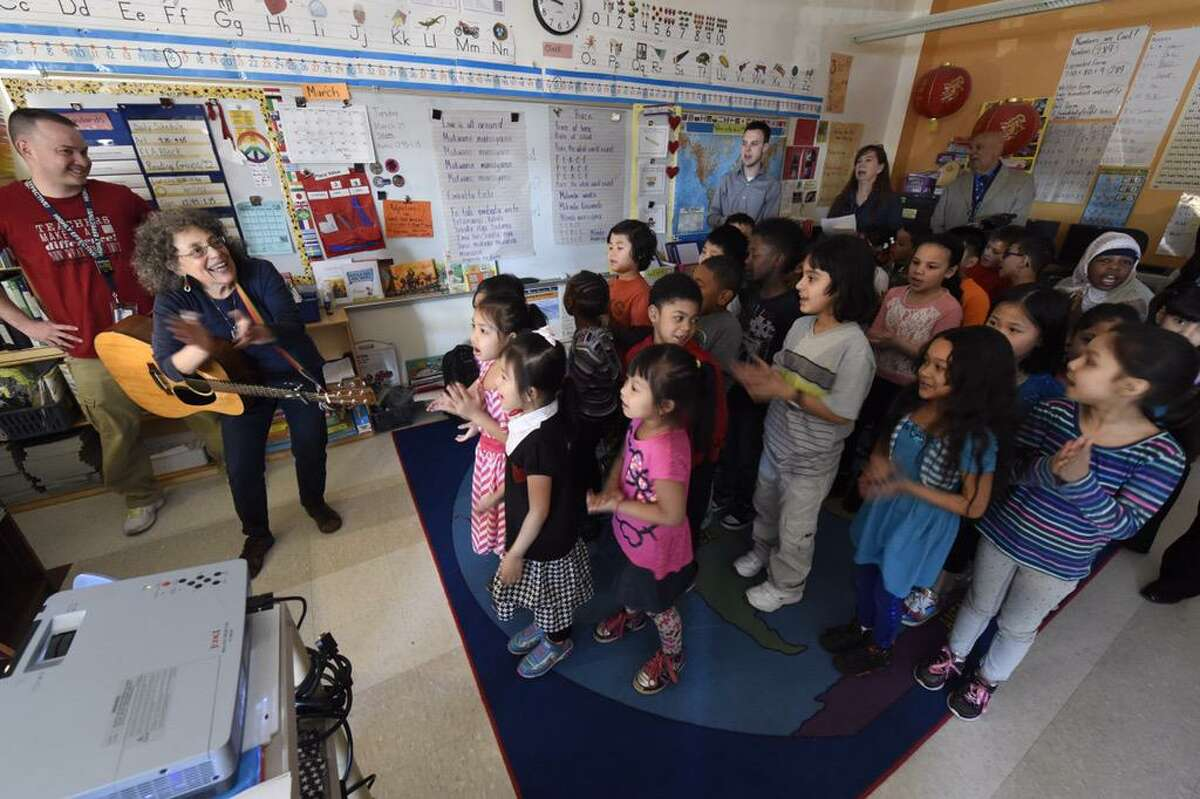 Susan Fowler's second grade in Albany's Delaware Community School clap along as Ruth Pelham plays her guitar and sings in their class on Tuesday. Earlier, the children used Skype to talk with orphans in Kampala, Uganda, on Tuesday. (Skip Dickstein / Times Union)
