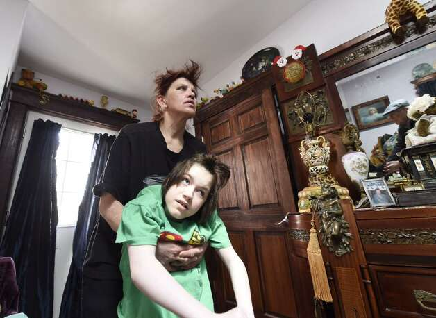 "Tanya Moran carries her disabled 14-year-old daughter, Rockelle ""Rocky"" Valentino, around their Albany home on Tuesday. Moran says someone took her daughter's wheelchair from her driveway. (Skip Dickstein / Times Union)"