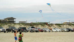 Two boys fly kites on the beach at Port Aransas.