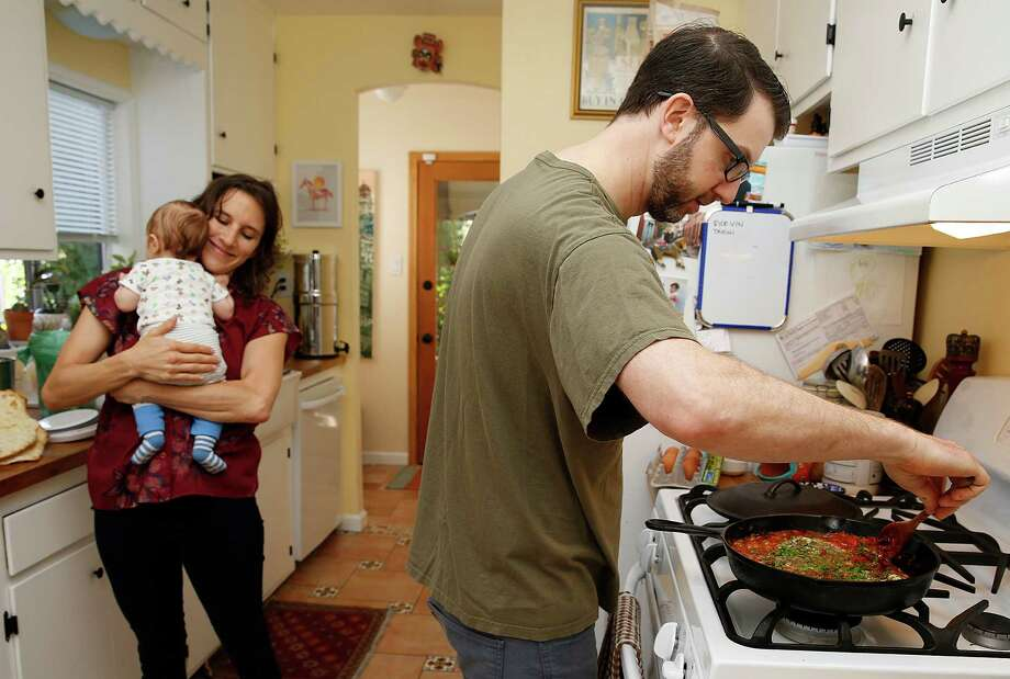 Blake Joffe prepares shakshuka, a Passover-suitable dish, in his home kitchen in Oakland as his wife, Amy Remsen, holds their 3-month-old son, Sterling. Photo: Liz Hafalia / The Chronicle / ONLINE_YES