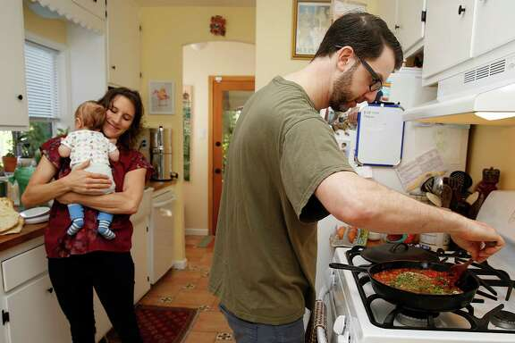 Blake Joffe prepares shakshuka, a Passover-suitable dish, in his home kitchen in Oakland as his wife, Amy Remsen, holds their 3-month-old son, Sterling.