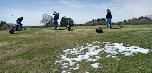 With snow still evident, from left, Tom Conti, Billy Comtois and Mike McCarthy get some practice on the driving range at Capital Hills at Albany golf course on opening day Thursday afternoon April 17, 2014 in Albany, N.Y.      (Skip Dickstein / Times Union) Photo: SKIP DICKSTEIN