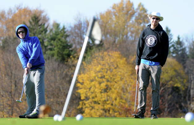UAlbany students Robert Cipolla, 20, left, and Deven Khosla, 21, practice putting before shooting a round of golf on Tuesday, Nov. 11, 2014, at Capital Hills Golf Course in Albany, N.Y. (Cindy Schultz / Times Union) Photo: Cindy Schultz / 00029431A