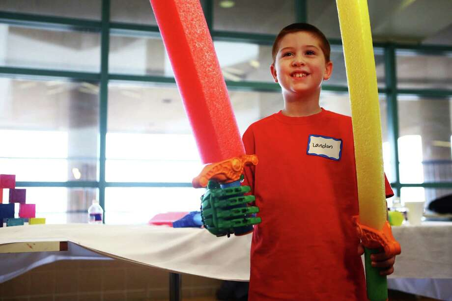 Landon Raines, 8, is finally able to hold a sword with his right arm thanks to a mechanical hand made out of custom plastic parts that were created on 3-D printers by e-NABLE volunteers from Rice University at Shriners Hospital for Children. Photo: Marie D. De Jesus, Staff / © 2015 Houston Chronicle