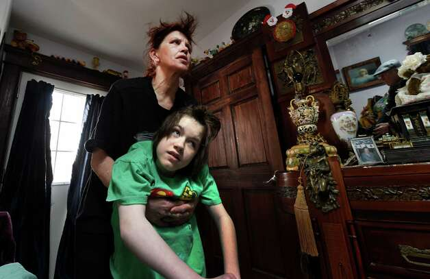 Tanya Moran holds her daughter Tuesday morning March 24, 2015, Rockelle Valentino, who's wheelchair was taken from their driveway last week  in Albany, N.Y.     (Skip Dickstein/Times Union) Photo: SKIP DICKSTEIN