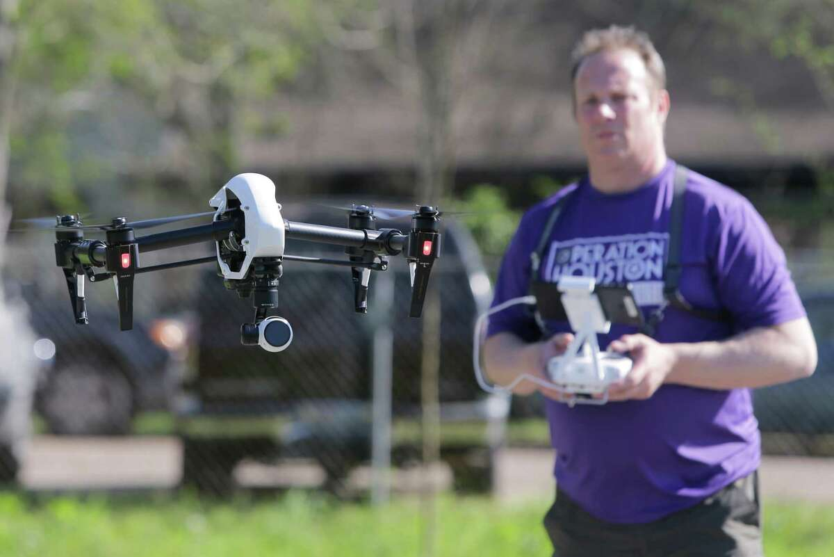 Tom McPhee of World Animal Awareness controls a drone to document stray dogs in Sunnyside.