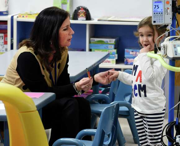 Child Life Specialist Angie Silipigno, left, works with patient Lexi Gurka Friday morning, Jan. 30, 2015, at the Melodies Center For Childhood Cancer and Blood Disorders at the Bernard & Millie Duker Children's Hospital at Albany Medical Center in Albany, N.Y.  (Skip Dickstein/Times Union) Photo: SKIP DICKSTEIN / 00030377A