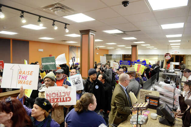 Minimum wage advocates occupy the Dunkin Donuts on the first floor of the Capitol during a rally in support of increasing the state wage to $15 per hour Monday, March 23, 2015, at the Capitol in Albany, N.Y. (Will Waldron/Times Union) Photo: WW, Albany Times Union / 00031142A