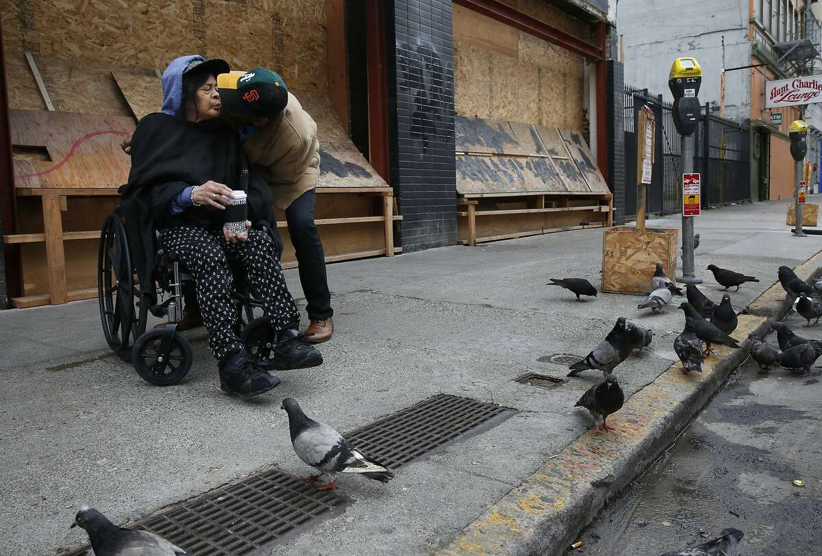 """Rodney """"Rock"""" Allen, right, leans in to kiss his wife Maria Quilala, as the two prepare to leave after feeding pigeons next to the construction site of an intended restaurant in the Tenderloin on Taylor and Turk Streets March 24, 2015 in San Francisco, Calif. Chefs Daniel Patterson and Roy Choi are starting a new restaurant on Turk and Taylor with the intent on serving inexpensive, sustainable and delicious food that is accessible to the local community."""