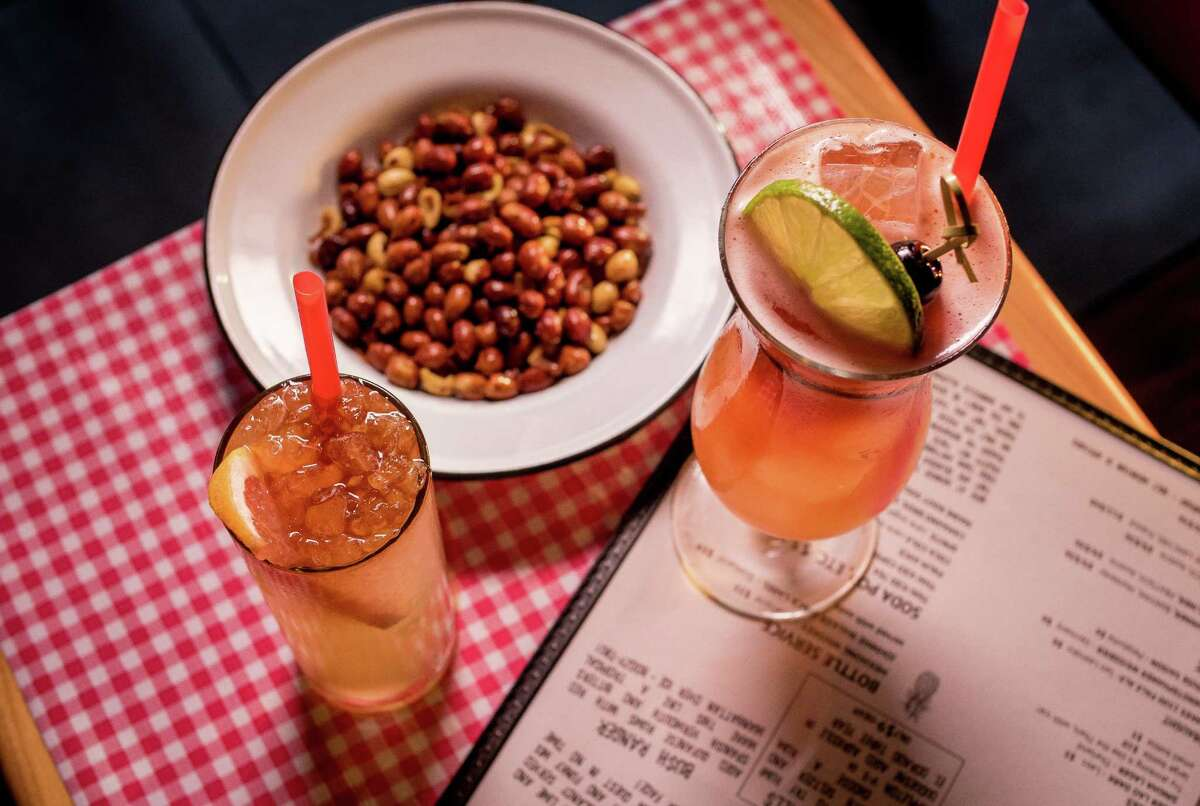 The Singapore Sling (right) and Witch Doctor cocktails with beer nuts at Hawker Fare in S.F.