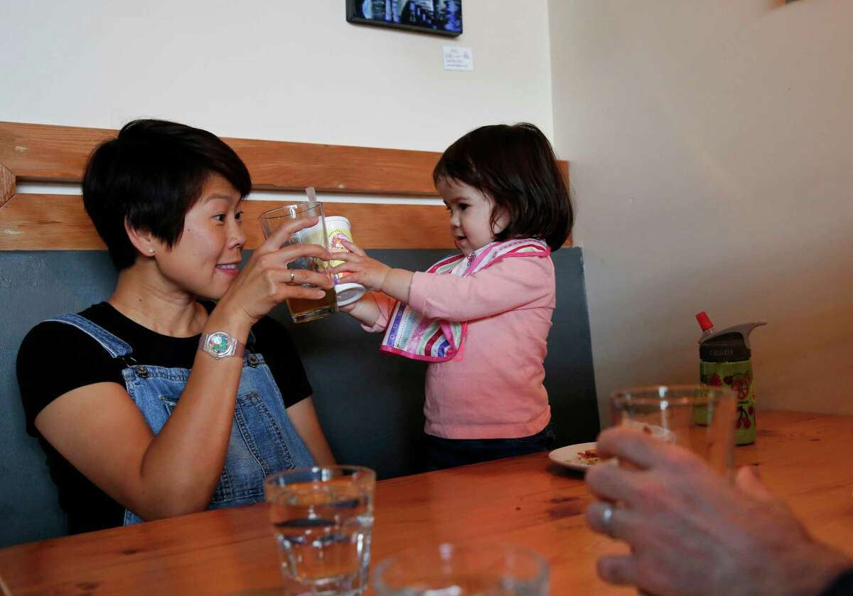 Cindy Cohen clinks glasses with daughter Vivienne, 1, as husband, Fred Cohen, sits across from them at Sunset Reservoir Brewing Co. The restaurant-brewery opened recently on Noriega in the Sunset District.