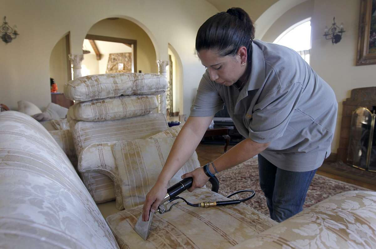 Rosa Sanchez, of Homejoy, cleans a sofa for Rie Yamazaki-Bach in San Francisco, Calif. on Tuesday, Oct. 28, 2014. Many homeowners are turning to Homejoy to connect with maintenance services such as carpet cleaning, plumbing and painting.