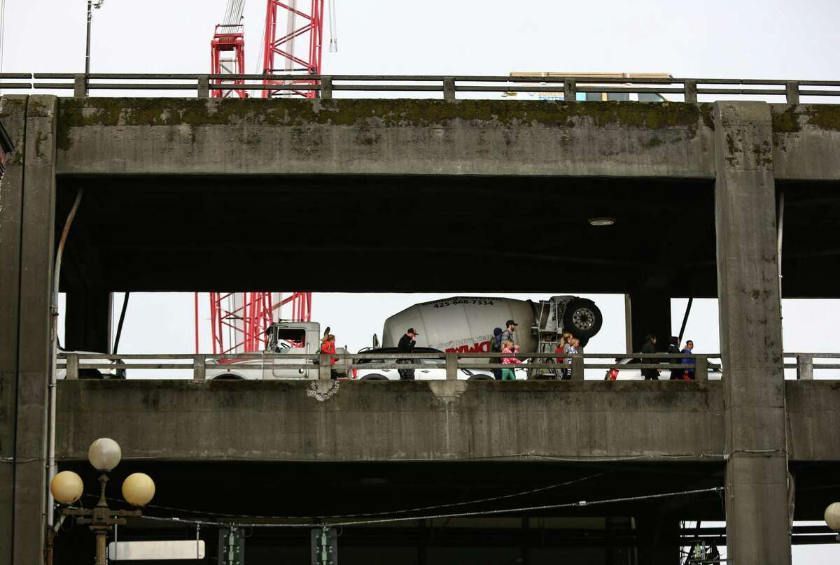 People walk along the Alaskan Way Viaduct Tuesday afternoon after traffic is hamstrung by an overturned semi truck in the southbound lanes at South Atlantic Street.