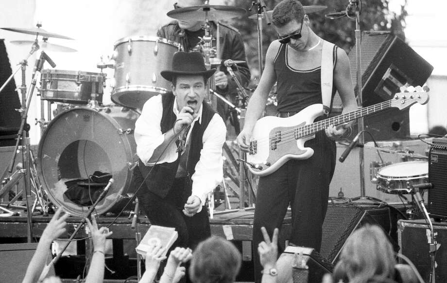 "Nov. 11, 1987: U2 singer Bono and bassist Adam Clayton entertain San Franciscans during a free concert in San Francisco's Justin Herman Plaza. The concert — and Bono's spray painting of the Vaillancourt Fountain — showed up in the movie ""Rattle and Hum."" Photo: Fred Larson / The Chronicle / ONLINE_YES"