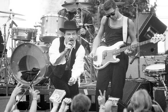 "Nov. 11, 1987: U2 singer Bono and bassist Adam Clayton entertain San Franciscans during a free concert in San Francisco's Justin Herman Plaza. The concert — and Bono's spray painting of the Vaillancourt Fountain — showed up in the movie ""Rattle and Hum."""