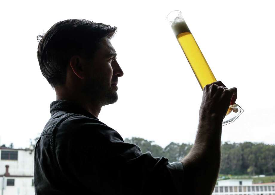 Tyler Catalana, co-founder of Fort Point Brewery in the Presidio, inspects a cylinder of beer at the brewery. Photo: Russell Yip / The Chronicle / ONLINE_YES