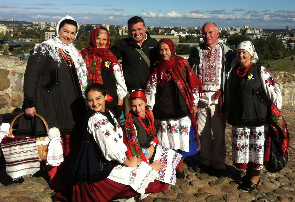 Chronicle Travel Editor Spud Hilton poses with a group of Ukrainian folk singers in traditional costumes at Vilnius Castle in Vilnius, Lithuania.