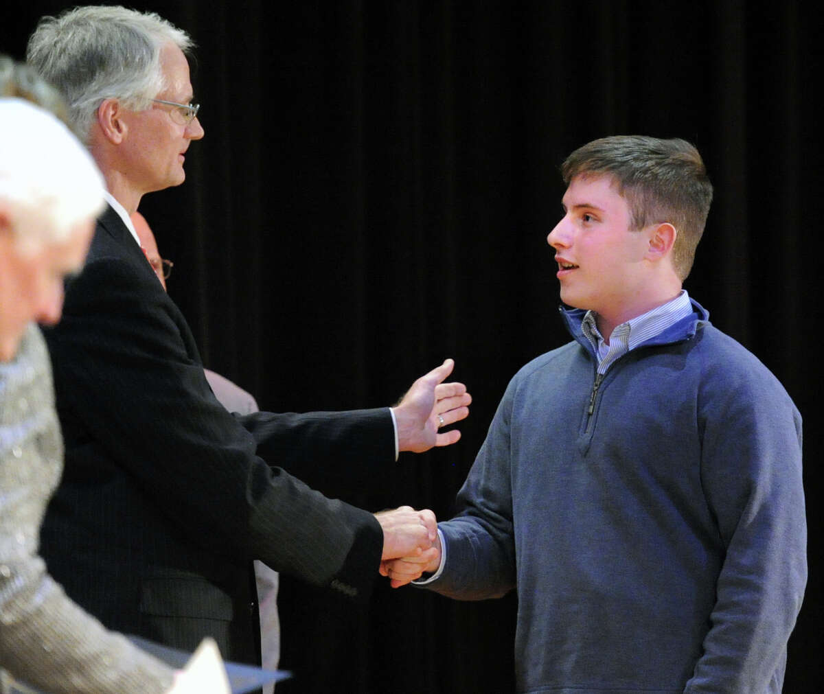 Superintendent of Schools William McKersie shakes hands with Greenwich High School student Peter Russell, right, who was one of the students honored during the Greenwich Public Schools Community Service Awards ceremony at Western Middle School in Greenwich, Conn., Tuesday, March 24, 2015. The awards are given to students based on participation in service activities that help to improve both their school and community.