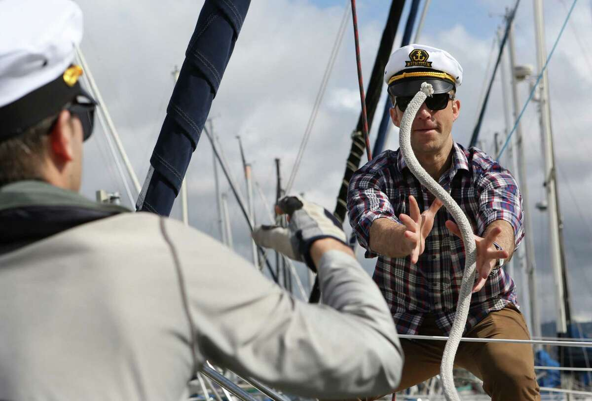 Jacob Best (left) tosses the rope to Charlie Seltzer as they prepare to set sail for the day on Dan Knox's 36-foot sailboat from Marina Village, Alameda on Sunday, March 22, 2015.