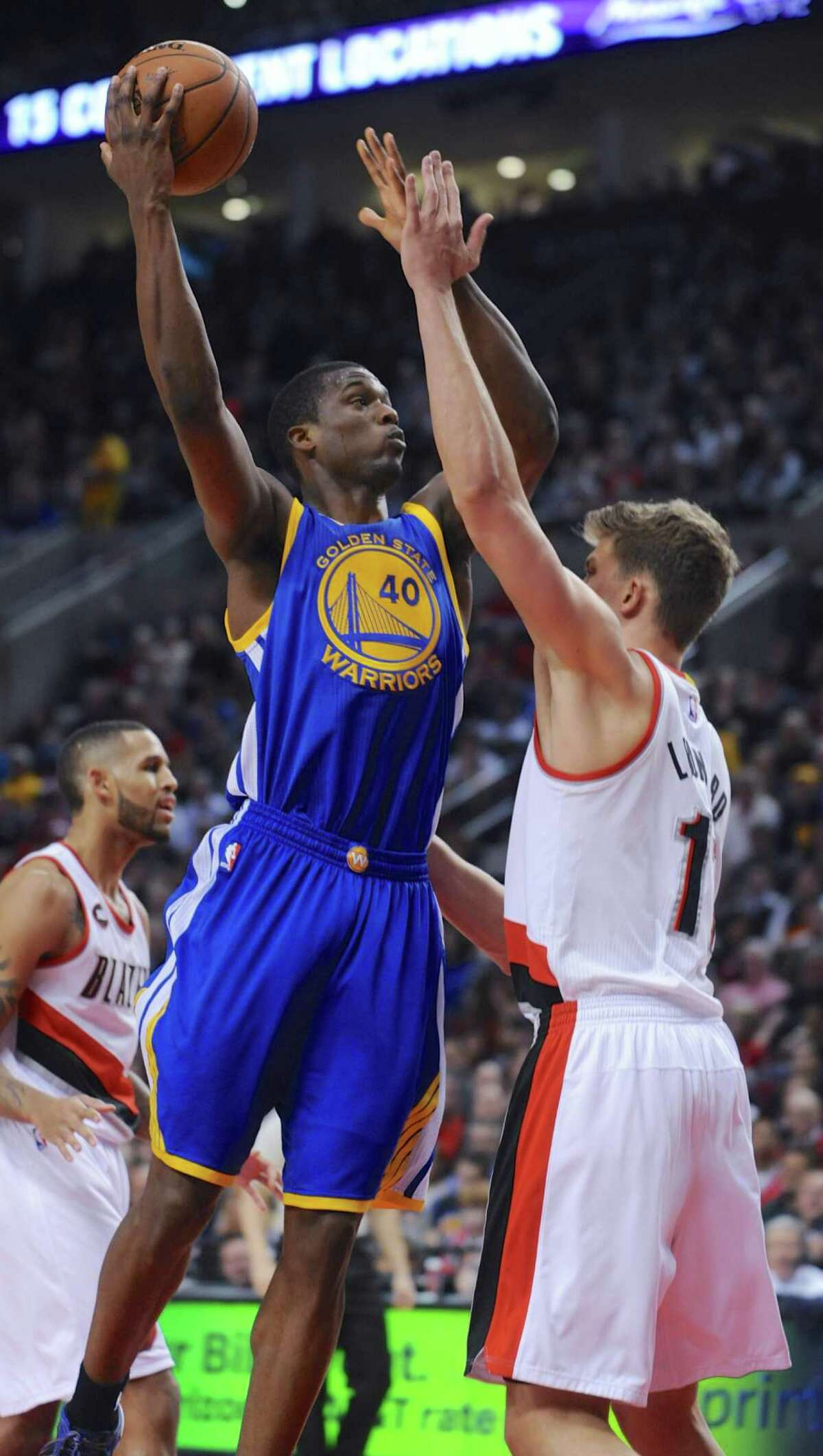 Golden State Warriors' Harrison Barnes (40) shoots against Portland Trail Blazers' Meyers Leonard (11) during the first half of an NBA basketball game in Portland, Ore., Tuesday, March 24, 2015. (AP Photo/Greg Wahl-Stephens)