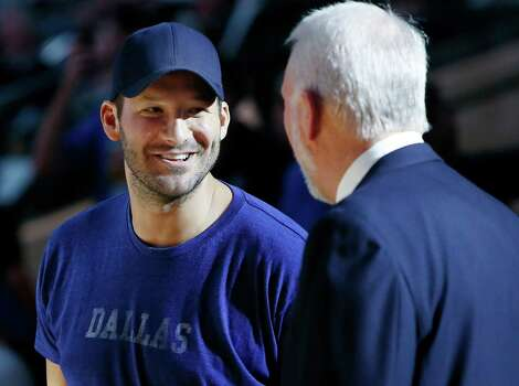 Dallas Cowboys quarterback Tony Romo and Gregg Popovich greet each other before the start of Tuesday's game. Photo: Brandon Wade /Associated Press / FR168019 AP