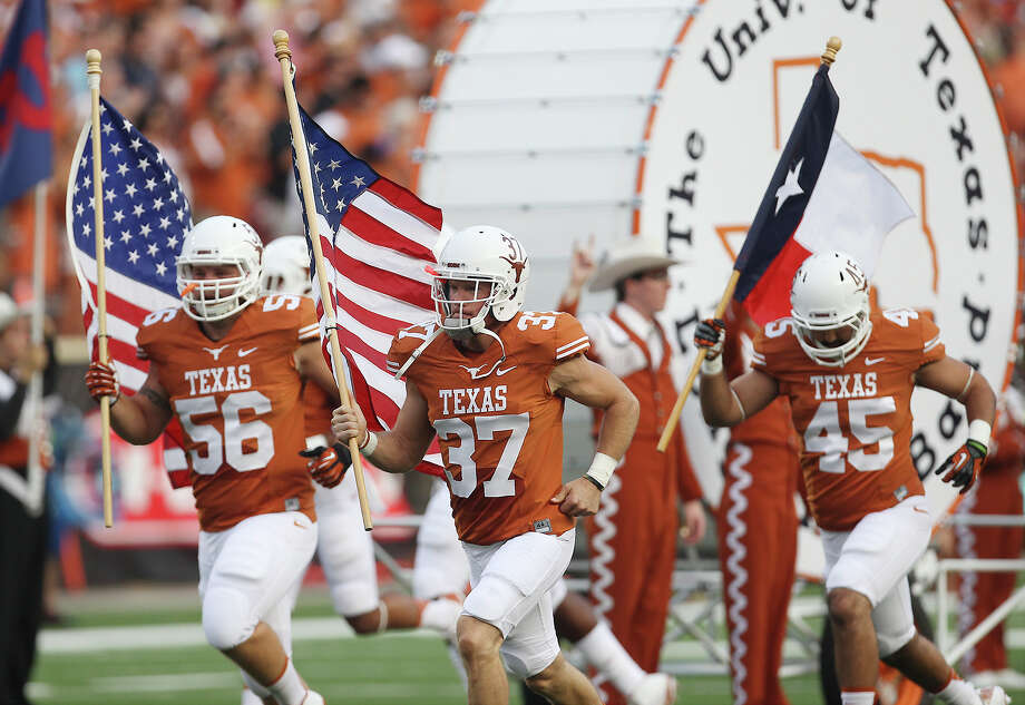 Texas' Nate Boyer (37) leads the team out with the U.S. Flag before the game against Ole Miss in the first half in Austin on Saturday, Sept. 14, 2013. (Kin Man Hui/San Antonio Express-News) Photo: Kin Man Hui, Staff / San Antonio Express-News / ©2013 San Antonio Express-News