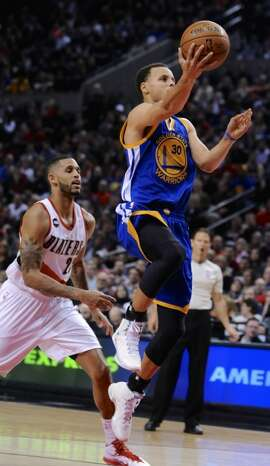 Golden State Warriors' Stephen Curry (30) shoots against Portland Trail Blazers' Allen Crabbe (23) during the first half of an NBA basketball game in Portland, Ore., Tuesday, March 24, 2015.