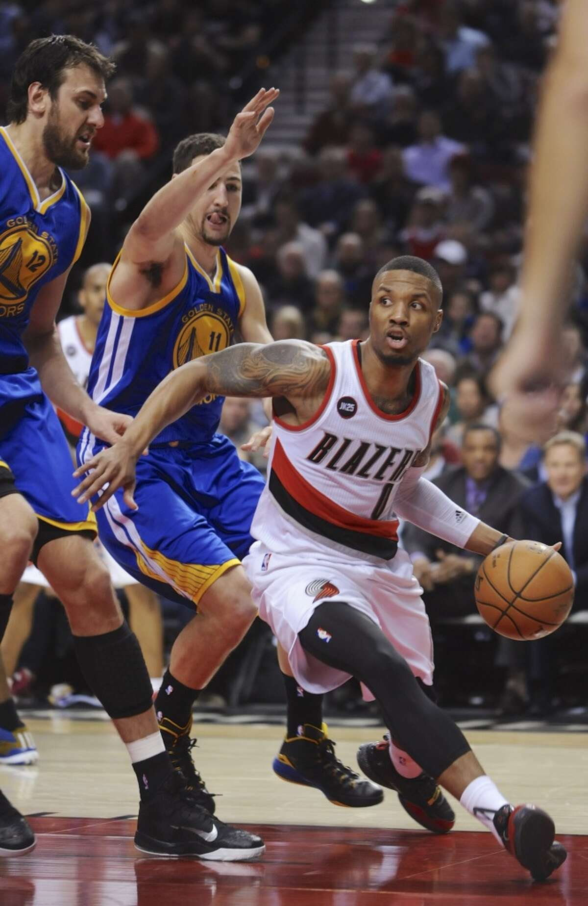 Portland Trail Blazers' Damian Lillard (0) drives against Golden State Warriors' Andrew Bogut, left, and Klay Thompson during the second half of an NBA basketball game in Portland, Ore., Tuesday, March 24, 2015.