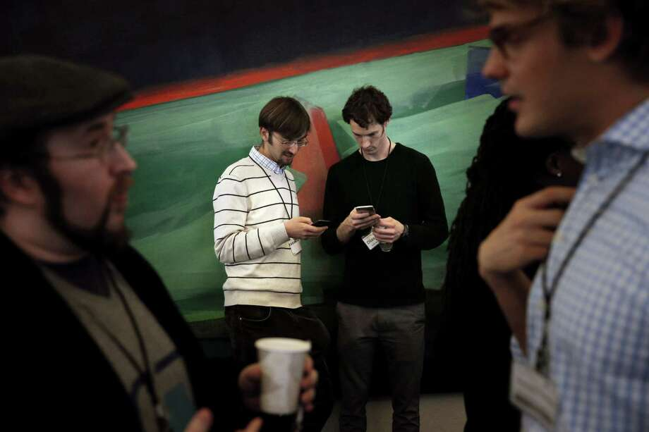 Ivan Dimov and John Waldeisen of Diassess, check their phones during a break of Y Combinator's Demo Day at the Computer History Museum in Mountain View Calif., on Tuesday, March 24, 2015. The two had presented their company's product, a test kit that allows any cell phone to perform rapid DNA-based disease detection using urine or saliva. Photo: Carlos Avila Gonzalez / The Chronicle / ONLINE_YES