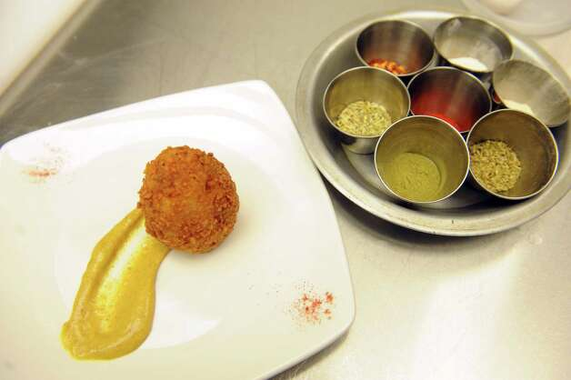 A finished plating of Scotch eggs next to the spices used in the sausage at The Shop on Thursday March 19, 2015 in Troy, N.Y.  Scotch eggs are made by wrapping a soft boiled egg in sausage and breading and then deep-frying. (Michael P. Farrell/Times Union) Photo: Michael P. Farrell / 00031078A