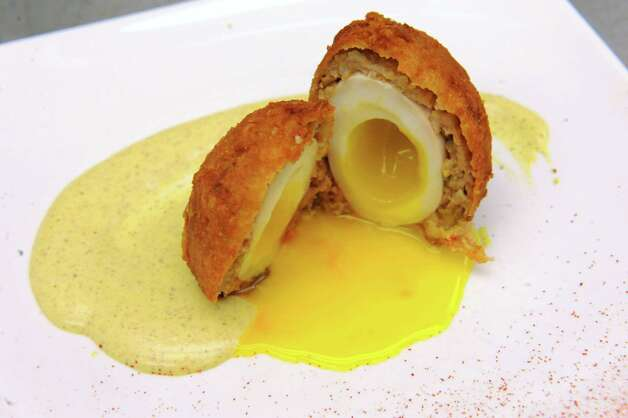A finished plating of Scotch eggs at The Shop on Saturday March 21, 2015 in Troy, N.Y.  Scotch eggs are made by wrapping a soft boiled egg in sausage and breading and then deep-frying. (Michael P. Farrell/Times Union) Photo: Michael P. Farrell / 00031135A