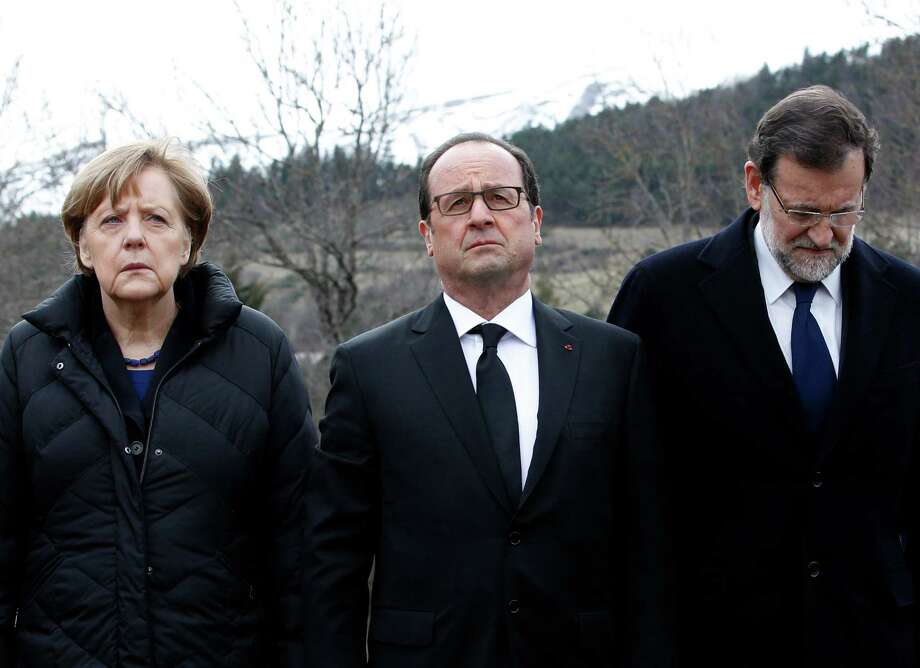 German Chancellor Angela Merkel, left, French President Francois Hollande, center, and Spanish Prime Minister Mariano Rajoy pay respect to victims in front of the mountain where a Germanwings jetliner crashed Tuesday, in the French Alps. Photo: Christophe Ena / Associated Press / AP