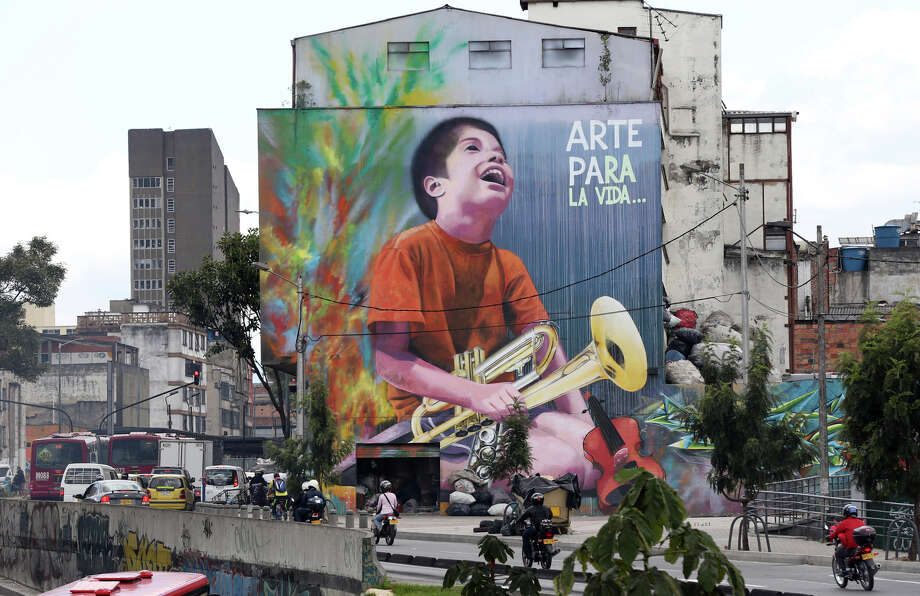 "A mural of a boy holding an instrument, with a message that reads ""Art for life,"" covers a wall in Bogota. Such art provides a welcome relief amid gray skies and the city's monochromatic red brick architecture. Photo: Fernando Vergara / Associated Press / AP"