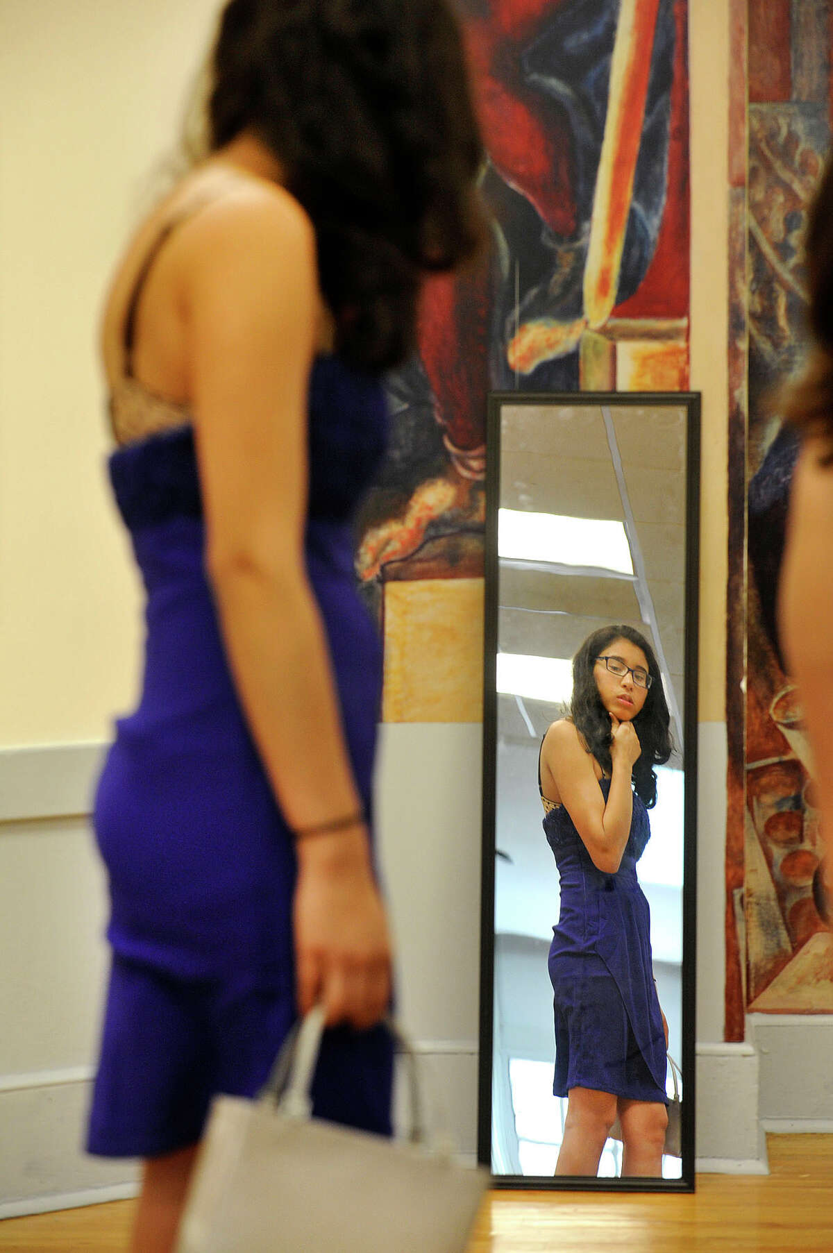 Stamford High junior Susana Cevallos looks at herself in a mirror after trying on a dress during the second annual Cinderella Project prom dress sale at Stamford High School in Stamford, Conn., on Wednesday, March 25, 2015. Many dresses and tuxedos normally sell for hundreds of dollars but are available through the Cinderella Project for $20 or under. All money from the sales goes into a fund for other prom-related costs for students. Organizer Holly Hyman says she is selling nearly 300 dresses and tuxedos that were donated from a handful of local organizations and individual donors. She will be at Westhill High School on Wednesday, April 8 from 7 a.m. to 3 p.m. For more information or to donate dresses or tuxedos, email Holly at hhman@optonline.net.