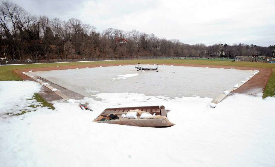 Snow is visible near home plate as a tarp covers a portion of the infield of the baseball field at Greenwich High School, Greenwich, Conn., Wednesday, March 25, 2015. Photo: Bob Luckey / Greenwich Time