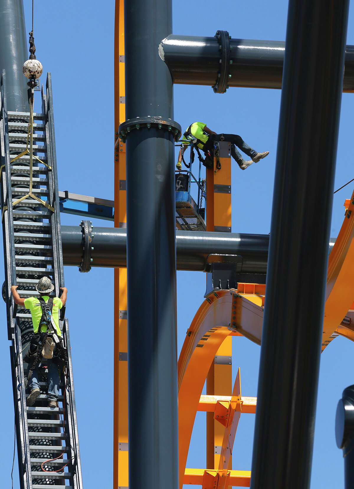 A piece of stairwell (left) is hoisted into place Wednesday March 25, 2015 on a new roller coaster ride at Six Flags Fiesta Texas. The roller coaster, called BATMAN: The Ride, is known as a 4D Wing coaster and lifts riders up 120 feet. Riders are flipped head-over-heels and will experience tumbling and unexpected drops along the way. The attraction is based on the Batman comic and offers immersion into the Batman storyline. The ride uses magnetic technology and has two beyond 90 degree drops giving the sensation of free-falling. The attraction has five vehicles with eight passengers each and will open in early summer 2015.