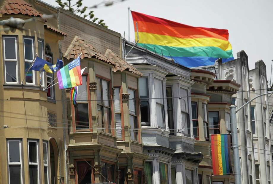 The iconic rainbow flag that flies over Harvey Milk Plaza is seen behind storefronts and apartments down Castro Street June 10, 2014 in San Francisco, Calif. The rainbow flag as a symbol for the LGBT community was originally created in San Francisco. The National Park Service is starting a project that will designate historically significant LGBT sites. Some of the many possible historic places in the city include Castro Camera, Harvey Milk Plaza, North Beach and the site of Black Cat Cafe. Photo: Leah Millis / The Chronicle / ONLINE_YES