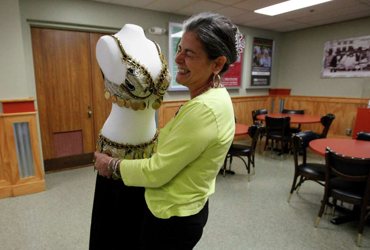 Jo Ann Andera puts away a mannequin adorned with her belly dancing outfit, whhich she once wore as a dancer at the Texas Folklife Festival before she became the event's director.