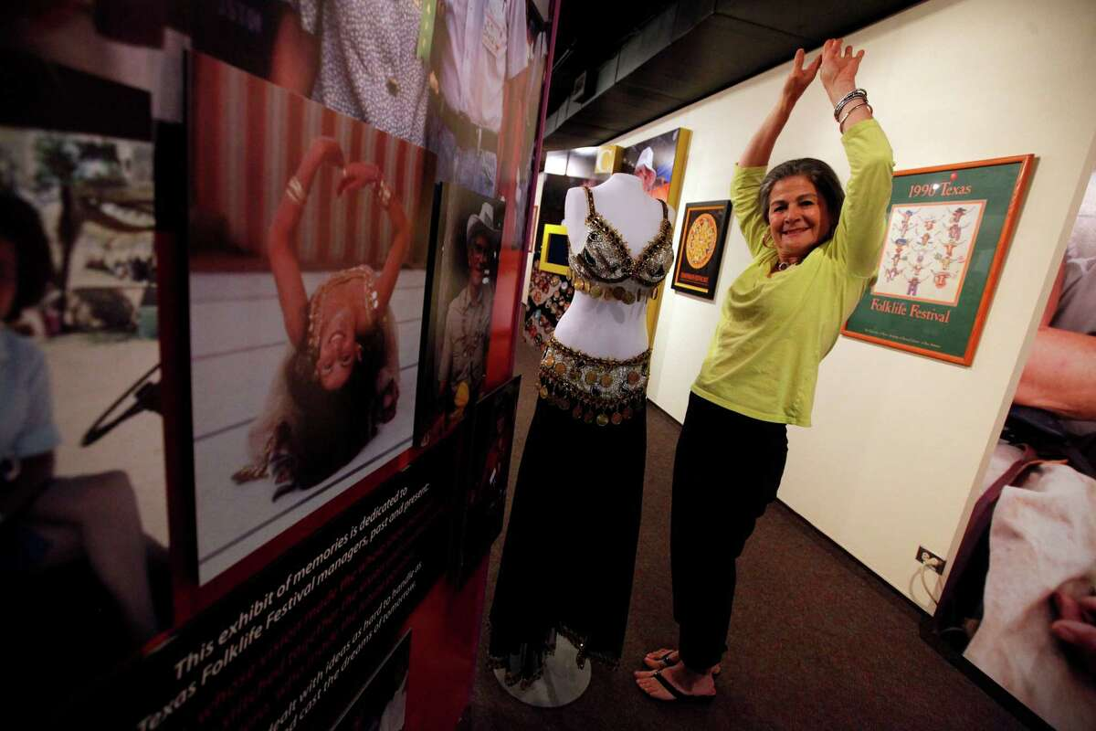 Jo Ann Andera strikes a pose beside an outfit she wore to belly dance and near a photo of her performing at the Texas Folklife Festival.