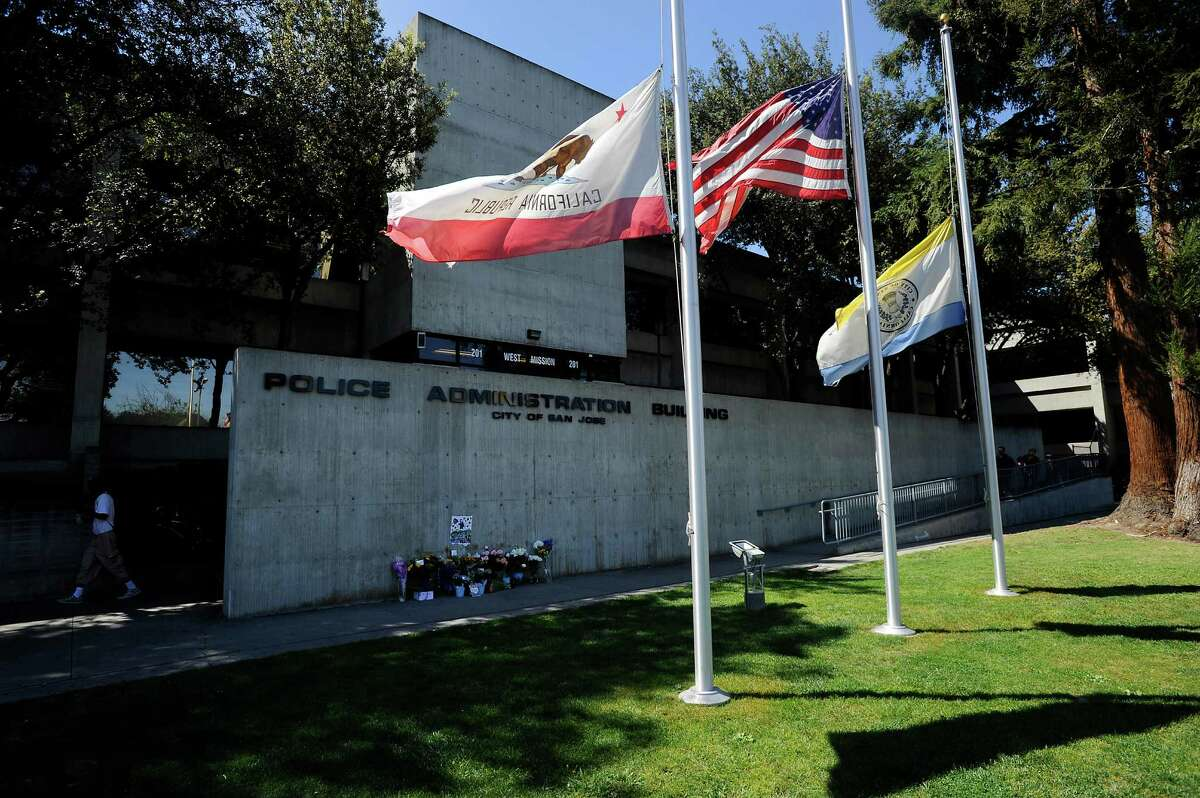 Flags file at half-staff next to a memorial for slain police Officer Michael Johnson in front of the San Jose Police Department headquarters.