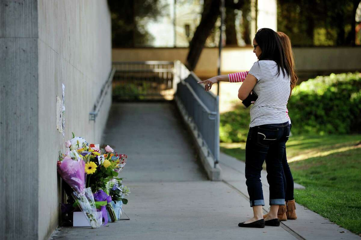 Sara Besinaiz, in front, and Eva Brown, who both work in the Hall of Justice, stop by a memorial for slain officer Michael Johnson in front of the San Jose Police Department headquarters in San Jose, CA, on Wednesday, March 25, 2015.