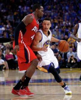 Golden State Warriors' Stephen Curry drives against Atlanta Hawks' Paul Millsap in 3rd quarter during NBA game at Oracle Arena in Oakland, Calif., on Wednesday, March 18, 2015.