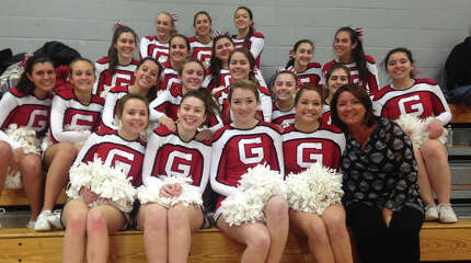 Mary Anne Catalano, front row, far right, gathers with her 2014-15 Greenwich High School cheerleading team. Catalano recently announced her retirement after being with the cheerleading program at GHS since 2000.