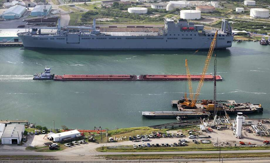 A tug boat pushes a barge for oil in the shipping channel past a military transport ship at the Port Corpus Christi. Without market constraints, oils from Eagle Ford and Bakken shales typically would attract higher, premium prices, said study author Ken Medlock, head of Rice University's Baker Institute for Public Policy. Instead, he said, the opposite is happening. He added that the steepest discounts are happening in the Eagle Ford. Photo: Express-News File Photo / ©2013 San Antonio Express-News