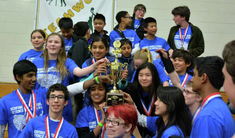 """Happy Bedford Middle School students display their trophy after capturing the state championship in the National Science Olympiad's Connecticut tournament in Farmington March 21. In winning the state title, Bedford's """"A"""" team will advance to the national championship at the University of Nebraska May 15 and 16. Photo: Westport News/Contributed Photo / Westport News"""