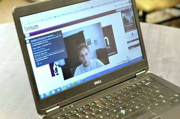 Karen Casper, seen on computer screen, talks with Linium Staffing's Miriam Dushane, managing director and Erin Gordon, a talent acquisition manager, on Thursday, Feb. 19, 2015, in Colonie, N.Y.   Linium Staffing is using this video technology in their interviewing process.    (Paul Buckowski / Times Union) Photo: PAUL BUCKOWSKI / 00030688A