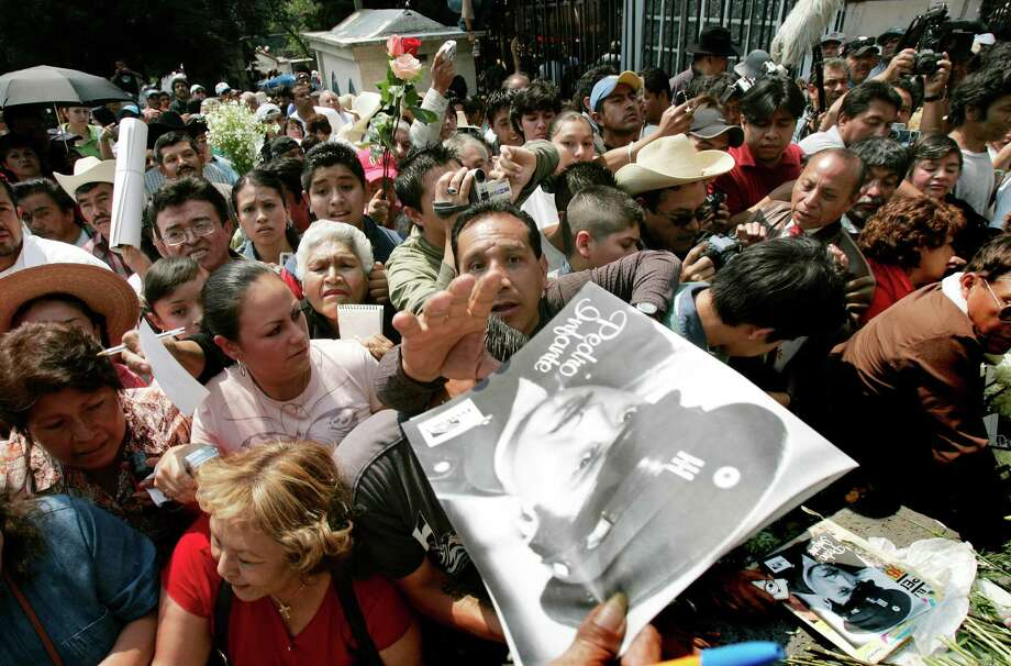 A man tries to reach an image of Pedro Infante at his grave in Mexico City, Sunday, April 15, 2007. Thousands of Mexicans visited the gravesite of the legendary actor and singer, who was killed 50 years ago in a plane crash in Merida, Mexico. Photo: Associated Press / AP2007