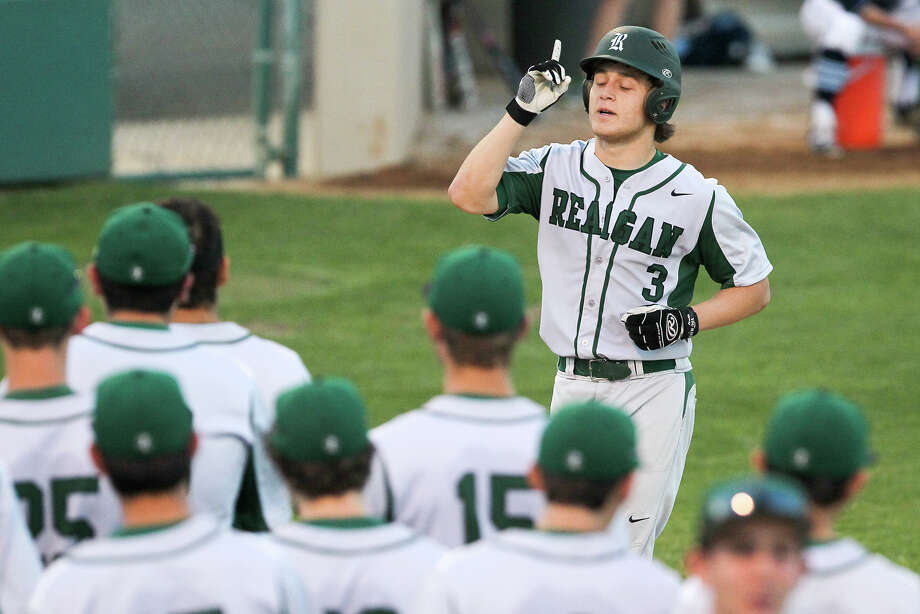 Reagan's Leyton Leone (top) points to the sky as he comes to home plate after hitting a fifth-inning home run during their District 26-6A game at the Blossom Athletic Complex on March 25, 2015. Reagan beat Johnson 9-3. Photo: Marvin Pfeiffer /San Antonio Express-News / Express-News 2015