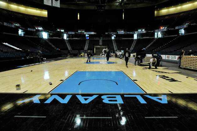 Times Union Center workers set up the basketball floor on Wednesday, March 25, 2015, in  Albany, N.Y.  The women's NCAA basketball tournament has games at the center on Saturday and Monday.  The floor is made special just for this regional tournament.  Monday night after the game the crews will get right back to work taking the floor apart and setting up for ice hockey.  (Paul Buckowski / Times Union) Photo: PAUL BUCKOWSKI / 00031176A