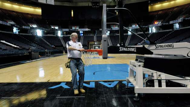Spalding Athletic dealer, Mike Kruse from Troy pulls a basketball hoop into place at the Times Union Center on Wednesday, March 25, 2015, in Albany, N.Y.  The women's NCAA basketball tournament has games at the center on Saturday and Monday.  Kruse, who is one of the NCAA tournament reps. for Spalding has to be at every practice and every game incase he is called upon to service the hoops.  At halftime of each game Kruse checks over the hoops to make sure everything is ok with the units.  (Paul Buckowski / Times Union) Photo: PAUL BUCKOWSKI / 00031176A